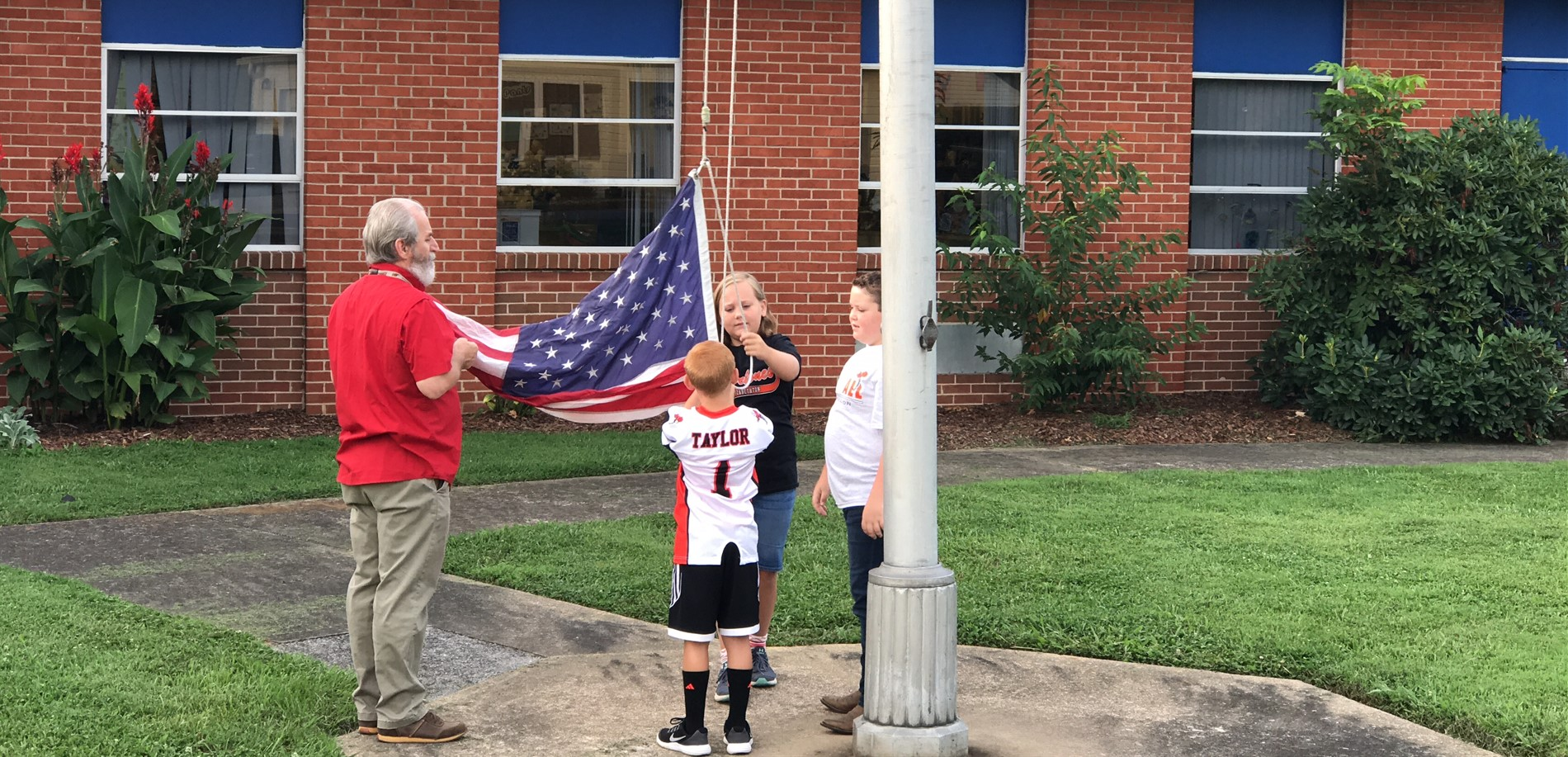 Students raising flag with teacher
