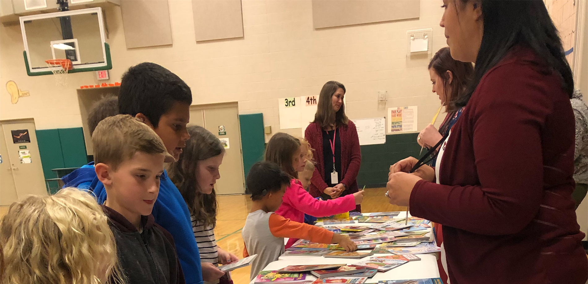 Students selecting books at table